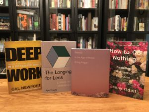 4 books on a table in front of a bookshelf